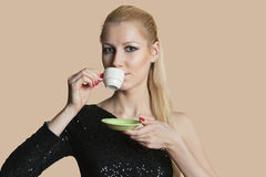 Portrait of beautiful young woman drinking tea over colored background Royalty Free Stock Photography