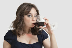 Portrait of beautiful young woman drinking wine against gray background Stock Image