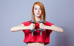 Portrait of beautiful young woman with dumbbells on the wonderfu. L grey studio background Royalty Free Stock Images