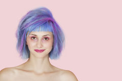 Portrait of beautiful young woman with dyed hair against pink background Royalty Free Stock Photography