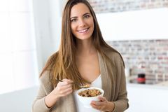 Beautiful young woman eating cereals at home. Royalty Free Stock Photography