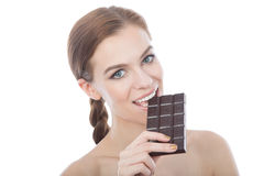 Portrait of a beautiful young woman eating a chocolate bar. A close-up portrait of a young woman eating a bar of dark chocolate. Isolated on white. Looking at Royalty Free Stock Image