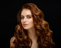 Portrait of a beautiful young woman with elegant long red shiny. Hair. Redhead girl over dark background Royalty Free Stock Photo