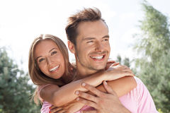 Portrait of beautiful young woman embracing man in summer park stock photography