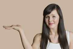 Portrait of a beautiful young woman with empty hand over colored background Royalty Free Stock Image