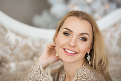 Portrait of beautiful young woman in evening dress smiles in Christmas Stock Images
