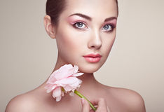 Portrait of beautiful young woman with flowers. Brunette woman with luxury makeup. Perfect skin. Eyelashes. Cosmetic eyeshadow stock photo