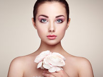 Portrait of beautiful young woman with flowers. Brunette woman with luxury makeup. Perfect skin. Eyelashes. Cosmetic eyeshadow stock photos