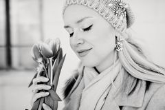 Beautiful blond woman in a knitted hat with tulip flowers. Black and white photo stock photography