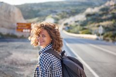 Portrait of a beautiful young woman with fluttering hair walking. On the road in the setting sun Royalty Free Stock Photo