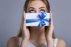 Portrait of a beautiful young woman with a gift in her hands, the girl funny closes her mouth with a box and looks up the concept royalty free stock photos