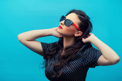 Portrait of the beautiful young woman in glasses on the black po Stock Photography