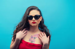Portrait of the beautiful young woman in glasses on the red vintage dress  on the blue background. Young female model Stock Photo