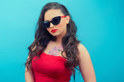 Portrait of the beautiful young woman  in glasses on the red vintage dress  on the blue background. Young female model Royalty Free Stock Images