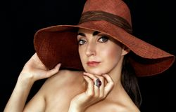 Portrait of a beautiful young woman in a hat on a black background royalty free stock photos