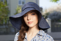 Portrait of girl with braid in hat. Portrait of a beautiful young woman in a hat and braid hairdo, looking at camera, outdoors Royalty Free Stock Photos
