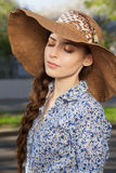 Girl in hat with closed eyes and braid. Portrait of a beautiful young woman in a hat with closed eyes and braid hairdo, outdoors Stock Images