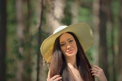 Portrait of a beautiful young woman with hat in forest Stock Photography