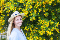 Portrait of a beautiful young woman in the hat with mimosa flowers stock photos