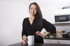 Portrait of beautiful young woman having coffee in kitchen Royalty Free Stock Images