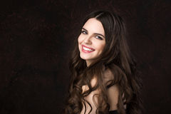 Portrait of a beautiful young woman with healthy long hair and beautiful smile on a dark background. royalty free stock photo