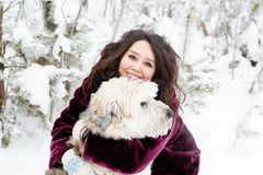 Portrait of beautiful woman with her South Russian Shepherd Dog on a background of winter coniferous forest. royalty free stock images