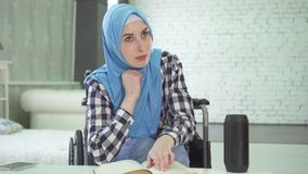 Beautiful young woman in hijab disabled person smiles, uses voice assistant for study and education. Portrait beautiful young woman in hijab disabled person