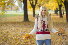 Portrait of beautiful young woman holding autumn leaves in park Stock Photo