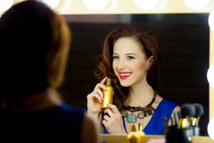Portrait of beautiful young woman holding bottle of perfume and Stock Images