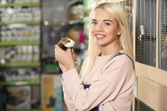 Portrait of beautiful young woman holding guinea pig. In pet shop Stock Photography
