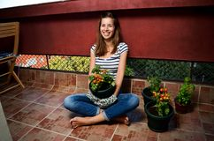 Home grown cherry tomatoes. Portrait of beautiful young woman holding home grown cherry tomatoes on her balcony royalty free stock images