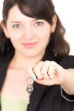 Portrait of beautiful young woman holding key. Concept of sale opportunity realtor investment isolated on white selective focus Stock Images