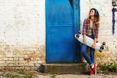 Young beautiful urban skate girl holding long-board in the street Royalty Free Stock Images
