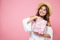 Portrait of a beautiful young woman holding present box, looking. Away, over pink background Royalty Free Stock Image