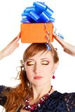 Portrait of a beautiful young woman holding a present on a head Royalty Free Stock Photo