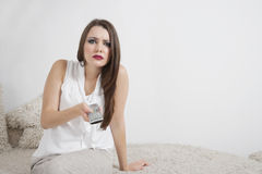 Portrait of beautiful young woman holding remote control Stock Photography