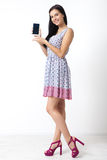 Portrait of beautiful young woman holding smartphone on white background Royalty Free Stock Photo