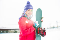 Portrait of beautiful young woman holding snowboard in snow Stock Image