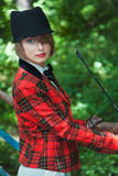 Portrait of beautiful young woman in horsewoman suit in forest Royalty Free Stock Images