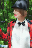 Portrait of beautiful young woman in horsewoman suit in forest Stock Image