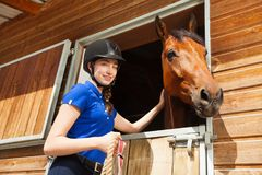 Happy jockey girl stroking horse at riding stable. Portrait of beautiful young woman in jockey skull stroking her bay horse at riding stable Stock Image