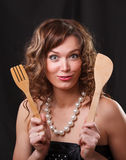 Portrait of a beautiful young woman with kitchen goods on a dark Stock Photos