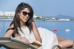 Portrait of beautiful young woman laying on a sunbed,reading a book Stock Images