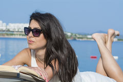 Portrait of beautiful young woman laying on a sunbed,reading a book Stock Photos