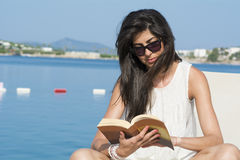 Portrait of beautiful young woman laying on a sunbed,reading a book Stock Photography