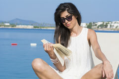 Portrait of beautiful young woman laying on a sunbed,reading a book Royalty Free Stock Images