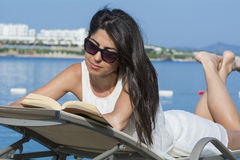 Portrait of beautiful young woman laying on a sunbed,reading a book. Reading a book on the beach .summer sea vacation Royalty Free Stock Image