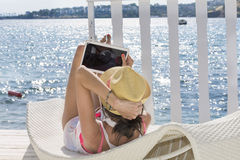 Portrait of beautiful young woman laying on a sunbed with tablet in the hand Stock Photography