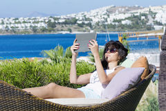 Portrait of beautiful young woman laying on a sunbed with tablet in the hand Stock Image