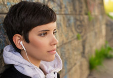 Portrait of beautiful young woman leaning on wall, listening music Stock Photos